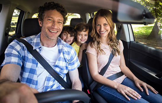 A happy family driving their car after receiving mobile auto detailing in Peoria IL
