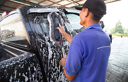 Man performing mobile auto detailing in Peoria IL on the exterior of a black truck